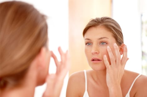 woman looking in the mirror *Not an actual patient | Knott Street Dermatology | Skin Care Center | Portland Oregon